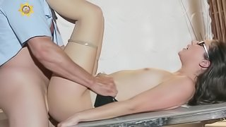 A brunette with glasses is fucked on the table really deeply