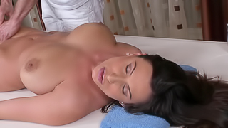 A busty woman is getting her large tits massaged in this video
